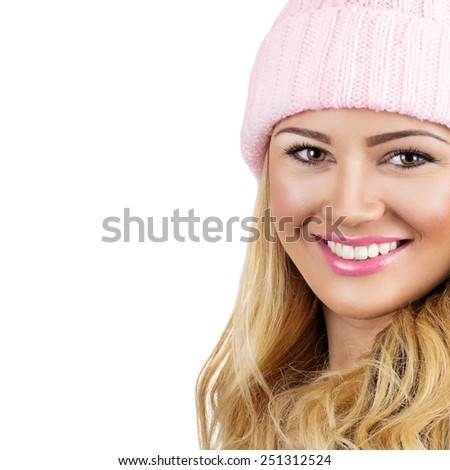 Closeup of beautiful blonde teenage girl with pink beanie hat and lips wearing neutral makeup smiling looking at camera isolated on white background. Retouched, square format, copy space. - stock photo