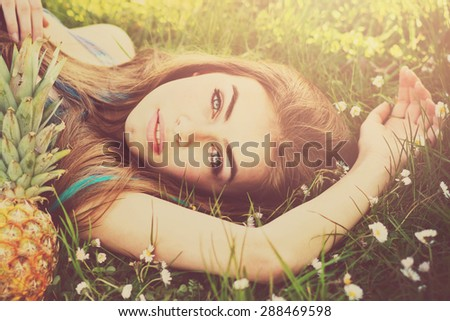 Closeup of beautiful blonde young fashion model's face. Gorgeous young woman lying in green grass in park on sunny summer day. Square format, retouched, vibrant colors. - stock photo