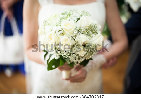 Closeup of beautiful bride in stylish white dress holding a roses bouquet