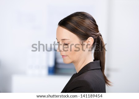 Closeup of beautiful businesswoman looking down in office - stock photo