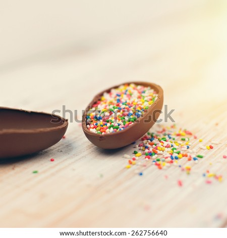 Closeup of beautiful chocolate Easter egg filled with colorful candy sprinkles. Closeup, pastel instagram look filter, shallow depth of field, selective focus, square format. - stock photo