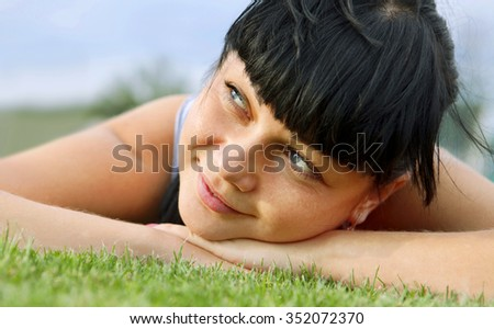 closeup of beautiful dreamy woman face that lies on grass - stock photo