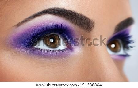 closeup of beautiful eyes with purple makeup - stock photo