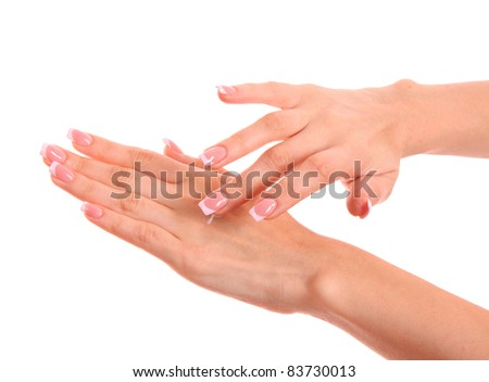 Closeup of beautiful female hands applying hand cream isolated on white background