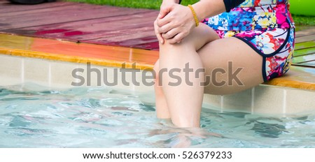 Closeup of beautiful female legs in water of a pool