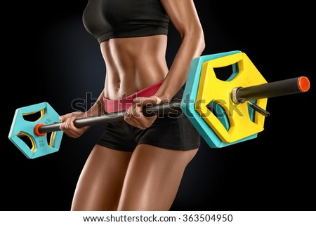 Closeup of beautiful fitness woman preparing to lift some heavy weights. Beautiful young woman exercises with barbell isolated over black background. - stock photo