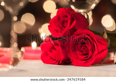 Closeup of beautiful fresh roses in a fine dinning setting. - stock photo