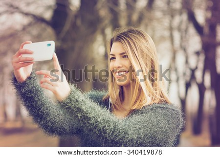 Closeup of beautiful happy blonde young Caucasian woman taking a selfie on smartphone outdoors in park in autumn. Horizontal, retouched, color filter applied. - stock photo