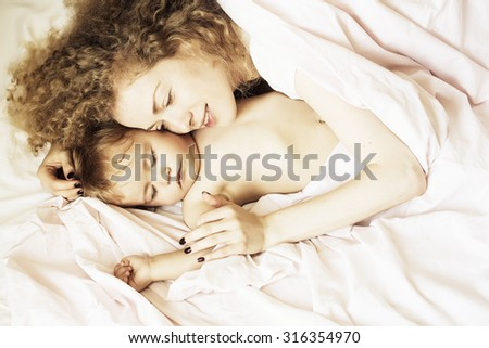 Closeup of beautiful loving mother with blonde curly hair embracing and sleeping with small tiny cute male lovely baby indoor in bed with white linen lying close to each other, horizontal picture - stock photo