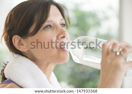 Closeup of beautiful mature woman drinking water after exercise outdoors