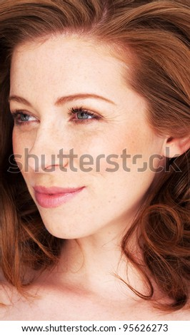 Closeup of beautiful natural redhead woman with smiling eyes looking to the side.