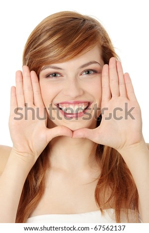 Closeup of beautiful smiling teen woman making frame on her face with her hands - stock photo