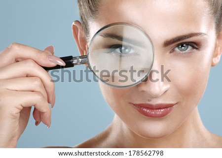Closeup of beautiful smiling woman looking trough glass on blue - stock photo