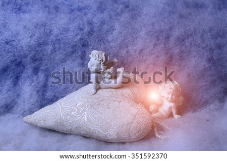 Closeup of beautiful soulful figurine composition of cupid angels for valentine day or christmas with small pillow in shape of heart lying on white wadding decorating snow with bright light spark - stock photo