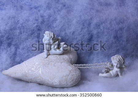 Closeup of beautiful soulful figurine composition of cupid angels for valentine day or christmas with small pillow in shape of heart lying on white wadding decorating snow, horizontal picture - stock photo