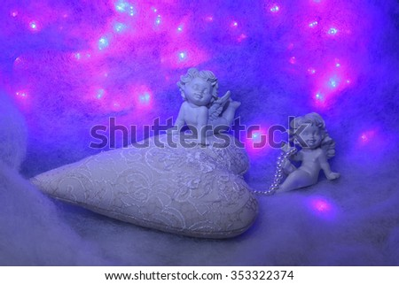 Closeup of beautiful soulful figurine composition of cupid angels for valentine day or christmas with small pillow in shape of heart lying on white wadding decorating snow with purple light sparks - stock photo