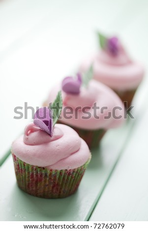 closeup of beautiful summer cupcakes with strawberry flavoured cream - stock photo