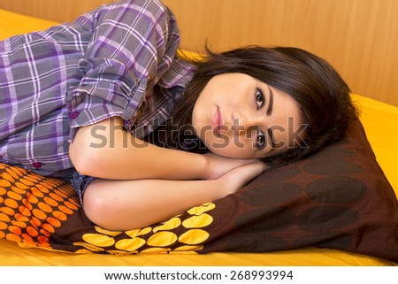 Closeup of beautiful teenage girl lying on bed in the bedroom - stock photo