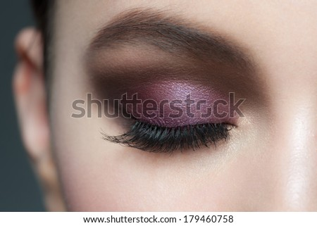 Closeup of beautiful woman eye with bright violet stylish makeup with long lashes - stock photo