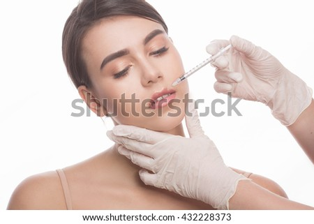 Closeup of beautiful woman getting injections in her lips. Full lips. Beautiful face and syringe. Plastic surgery and cosmetic injection concepts.