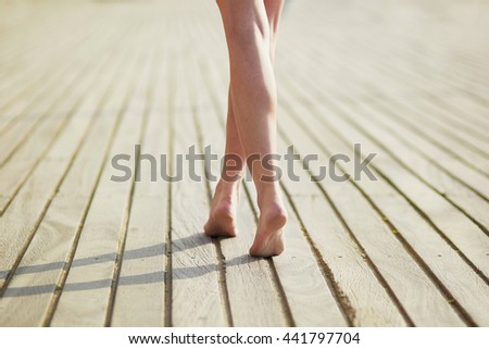 Closeup of beautiful woman leg's on wooden beach jetty. Barefeet on wooden planks. Unrecognizable person walking barefeet