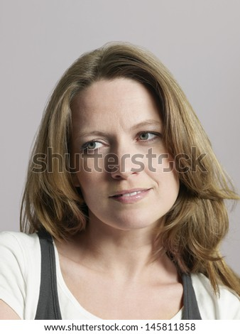 Closeup of beautiful woman looking away on colored background