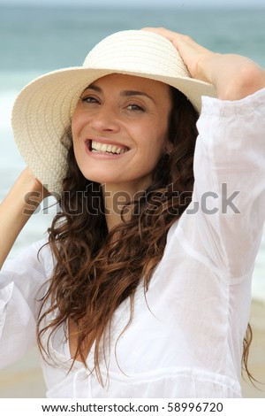Closeup of beautiful woman wearing straw hat - stock photo