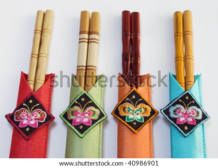 closeup of beautiful wooden chopsticks in colorful embroidered sleeves, isolated on light background - stock photo