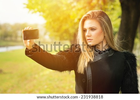 Closeup of beautiful young blonde Caucasian woman in black coat taking a selfie with smart phone in park in autumn. - stock photo