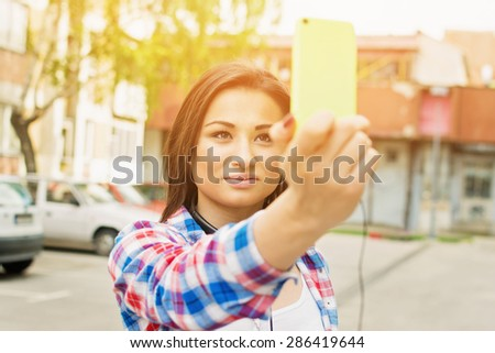 Closeup of beautiful young brunette mixed race woman taking a selfie with smart phone. Teenage girl in blue and red checkered shirt taking a self portrait with cellphone outdoors. - stock photo