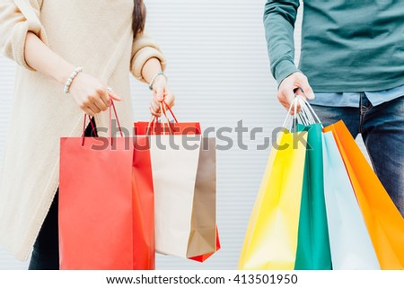 Closeup of beautiful young couple holding shopping bags