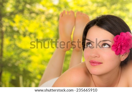 closeup of beautiful young girl wrapped in towel with flower on her head in outdoor spa - stock photo