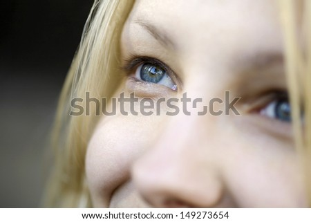 Closeup of beautiful young woman with blue eyes looking away - stock photo