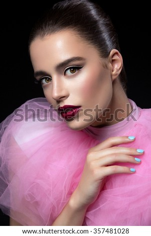 Closeup of beautiful young woman with dark red lips in pink lace fluffy collar over black background - stock photo