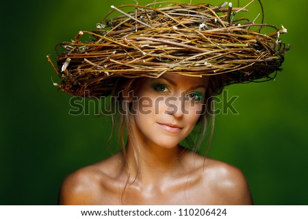 Closeup of beautiful young woman with fresh makeup and wicker nest on her head over green background - stock photo