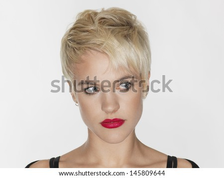 Closeup of beautiful young woman with red lips looking sideways on white background - stock photo