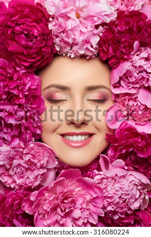 Closeup of beauty woman face with perfect skin and professional makeup in peony flowers with closed eyes