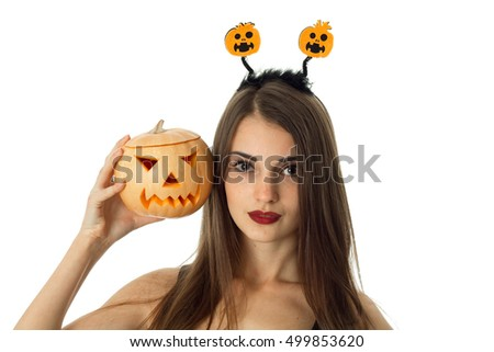 closeup of beauty woman in halloween style clothes with pumpkin in hands looking at camera in studio isolated on white