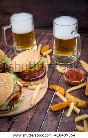 Closeup of beer and home made burgers on sesame buns with beef patties and fresh salad ingredients on wooden background - stock photo