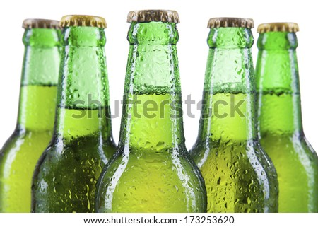 Closeup of beer bottles with condensation drops, isolated on white. - stock photo