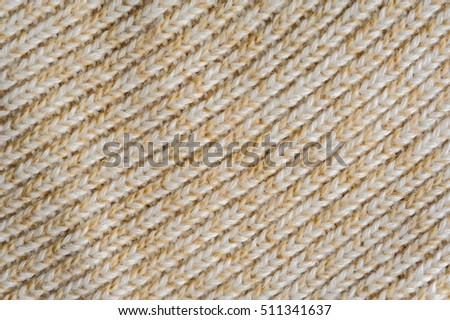Closeup of beige knitted woolen fabric texture for wallpaper or an abstract background.