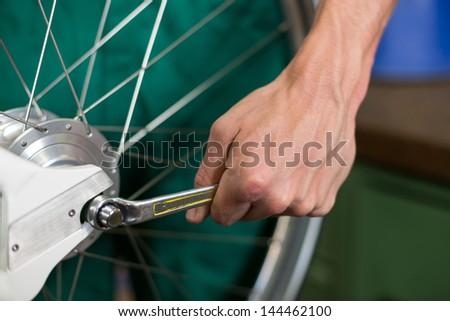 Closeup of bicycle mechanic with a wrench repairing bike wheel - stock photo