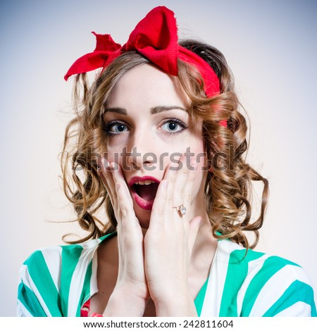 closeup of big blue eyes pretty girl with open mouth in surprise looking at camera over light copy space - stock photo