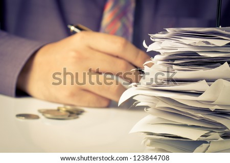 Closeup of bills in paper nail with hand calculating - stock photo
