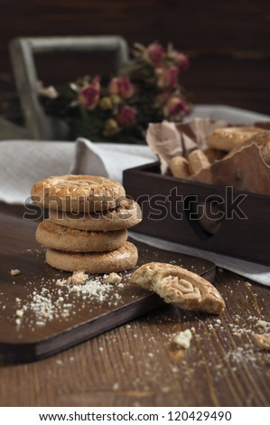 Closeup of biscuits stack and one broken cookie with crumbs on cutting board make in brown tones. - stock photo