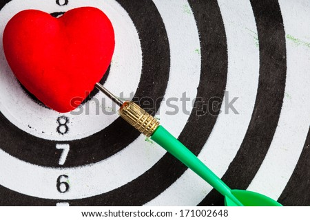 Closeup of black and white target with dart in red valentine heart love symbol as bullseye. Skeet trap shooting sport in valentines day.