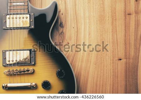 Closeup of black and yellow electric guitar on natural wooden surface - stock photo