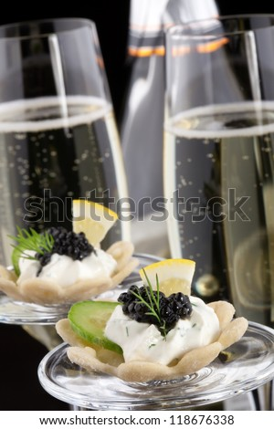 Closeup of black caviar on Creme Fraiche and flutes of Champagne over black background - stock photo