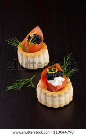 Closeup of black caviar on Creme Fraiche and smoked salmon canape over black background.