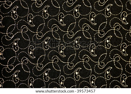 Closeup of black fabric with metallic gold embroidered design - stock photo